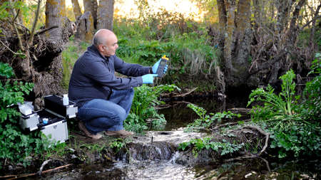Biologist that collects data on temperature of a water course for the analysis of its pollution and for the study of its features. Stock Photo