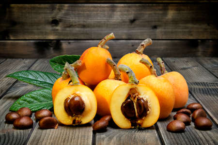 seasonality: Medlars produced with organic cultivation photographed on antique wood background Stock Photo