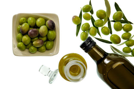 Shot from above of fresh olives freshly harvested and extra virgin olive oil isolated on white background