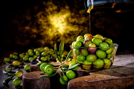 Pour the oil onto a bowl of fresh olives freshly picked on an antique wooden table.