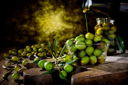 sardine: Pour the oil onto a bowl of fresh olives freshly picked on an antique wooden table.