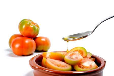 Pouring olive oil with spoon on a fresh tomato salad isolated on white background
