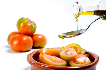 Close up of an ampoule pouring olive oil on a fresh tomato salad isolated on white background Stock Photo