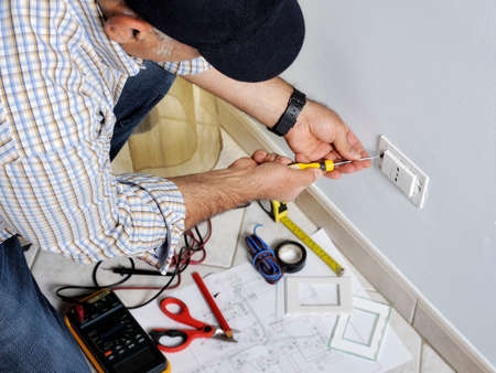 Electrician at work on switches and sockets of a residential electrical system. Stock Photo