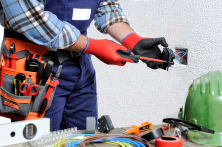 Electrician with hands protected by gloves and insulated tools works on a residential electrical installation.