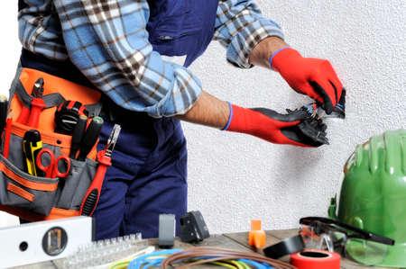 手袋および絶縁された用具によって保護される手を持つ電気技師は住宅の電気設備の安全規則を尊重する働く。