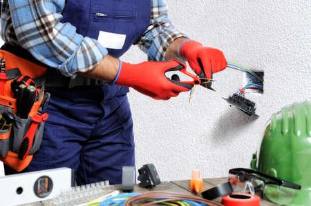 L'électricien avec les mains protégées par des gants et des outils isolés travaille en respectant les règlements de sécurité dans une installation électrique résidentielle.