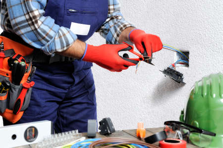 L'elettricista con le mani protette da guanti e strumenti isolati lavora nel rispetto delle norme di sicurezza in un impianto elettrico residenziale. Archivio Fotografico - 92173900