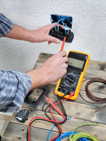 Young Electrician At Work Measures The Voltage Of A Residential