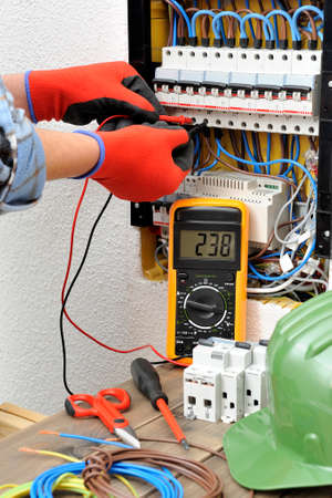 Young electrician technician measures with a multimeter the voltage in a electrical panel Standard-Bild