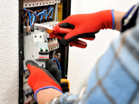 Young electrician technician introduces the electric cable into the clamp of the magnetothermic switch with an insulated clamp Stock Photo