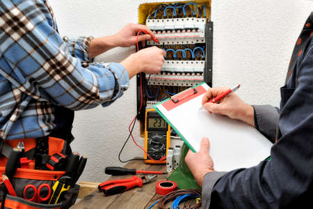 The engineer writes on a notepad the measurement of the voltage of the electrical panel detected by the young electrician Banque d'images