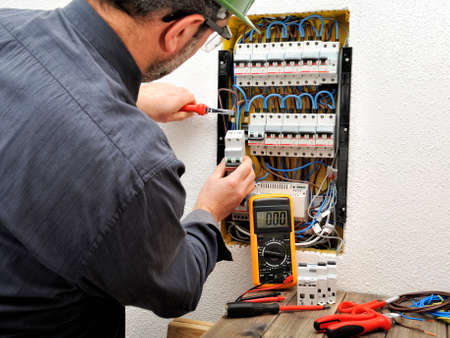 Electrician technician introduces the cable into the terminal of a magnetothermal switch of a residential electrical panel
