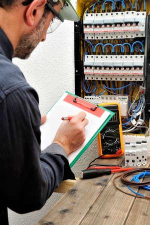 전기 기술자는 주거용 전기 패널에 수집 된 데이터를 노트북에 씁니다. 스톡 콘텐츠 - 93372032