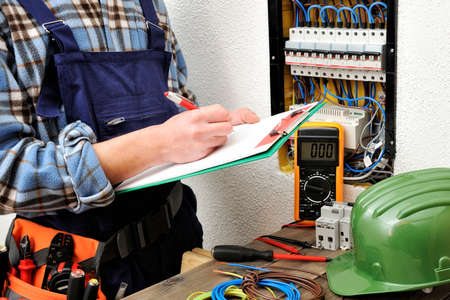 Young electrical technician writes in a notebook the data collected on a residential electric panel Banque d'images