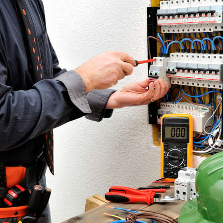 Elegant technical electrician fixing the cable into the terminal of a circuit breaker of a residential electrical panel