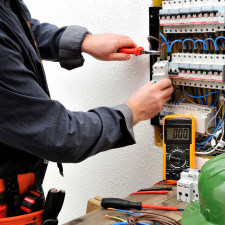 Elegant electrician technician introduces the cable into the terminal of a magnetothermal switch of a residential electrical panel