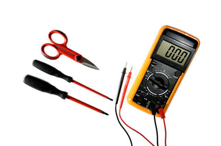 Multimeter, scissors and screwdrivers for working on a residential electrical installation photographed on a white background