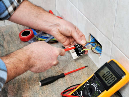 Electrician technician working on switches and sockets of a residential electrical system.