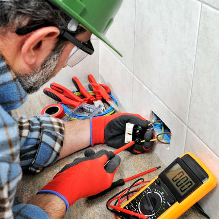 Electrician technician with gloves and safety instruments fixes the electric cable to the socket of a residential installation. Banco de Imagens