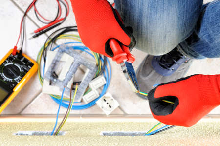 Electrician technician at work with pliers on the cable of in a residential electric installation