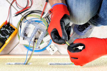 Electrician technician at work prepares the cable with hands protected by gloves in a residential electrical installation