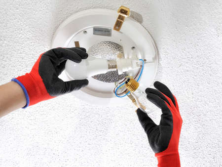 Electrician technician replaces the old filament bulb with a low consumption led bulb in a residential electrical system