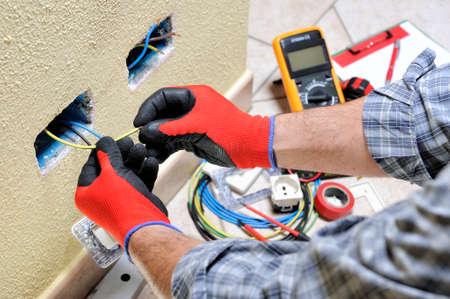 Elektriker-Techniker bei der Arbeit bereitet das Kabel mit den Händen vor, die durch Handschuhe in einer elektrischen Wohninstallation geschützt werden