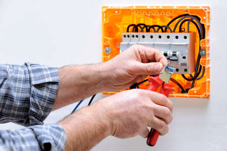 Electrician technician working on a residential electric panel, cuts the cable with a cable cutter