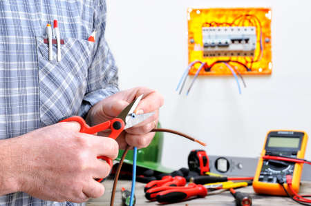Electrician technician at work in a residential electric installation, cuts the cable Stock Photo