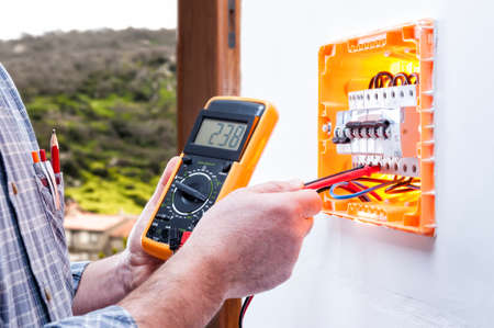 Electrician technician at work on a residential electrical panel, measures the voltage with the tester