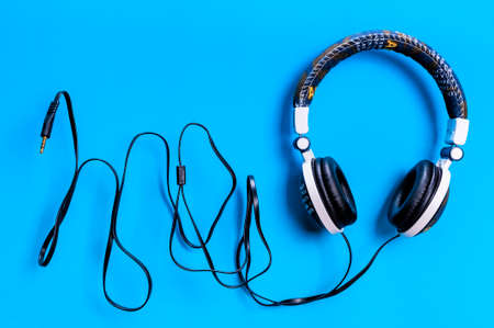 Top view of an audio headphone covered with fabric jeans photographed on a light blue background