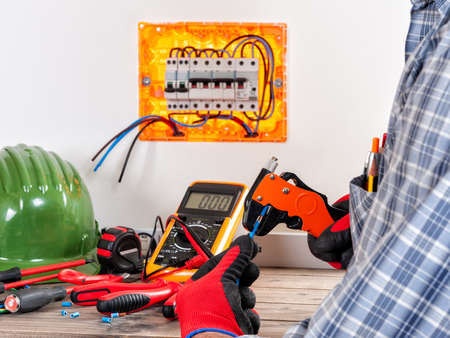Electrician technician at work in a residential electric system uses the wire stripper with his hands protected by gloves. Stock Photo