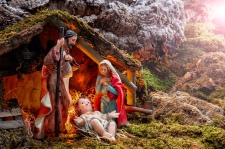Close-up of the Christmas Nativity scene. Hut with baby Jesus in the manger, with Mary and Joseph. Ray of light.