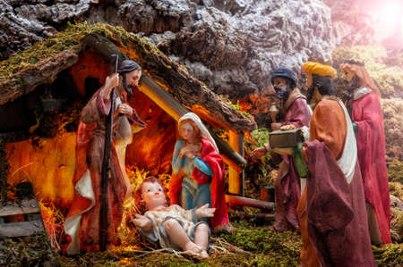Close-up of the Christmas Nativity scene. Hut with baby Jesus in the manger, with Mary, Joseph and the three wise men. Ray of light. Stock Photo