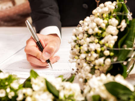 Detail of the hand of a groom who signs the marriage act Stock Photo
