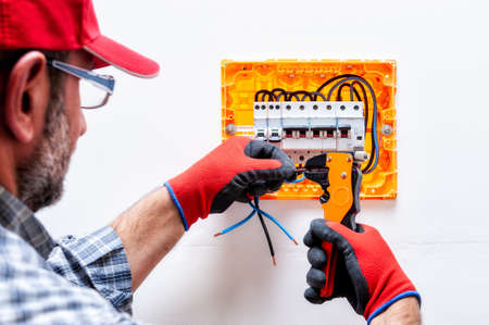 Electrician technician with glove-protected hands, works with the wire-cutter pliers in a residential electrical panel.
