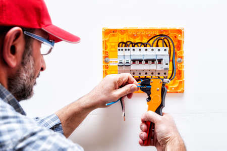 Electrician technician works with the wire cutter pliers in a residential electrical panel.
