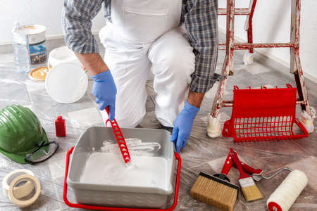 Caucasian house painter worker in white work overalls, mixes the paint in the container. Construction industry.
