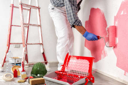 Caucasian house painter worker in white work overalls, with the roller painting the wall with colorful painting. Construction industry.