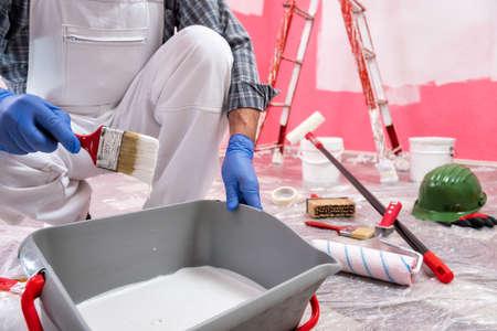 Kaukasischer Anstreicher in weißen Overalls, bereiten Sie die weiße Farbe vor, um die rosa Wand zu streichen. Bauindustrie. Arbeitssicherheit.