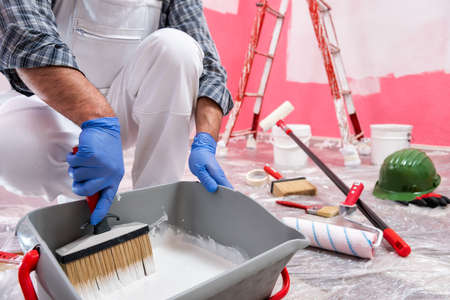 Caucasian house painter worker in white overalls, prepare the white paint to paint the pink wall. Construction industry. Work safety. Stock fotó