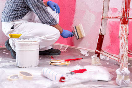 Caucasian house painter worker in white overalls, with the brush painting the pink wall with white paint. Construction industry. Work safety.