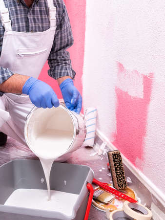 Caucasian house painter worker in white overalls, pour the white paint into the container. Construction industry. Work safety.