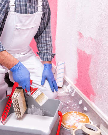 Caucasian house painter worker in white overalls, painting the pink wall with white paint using a small brush. Construction industry. Work safety. Фото со стока