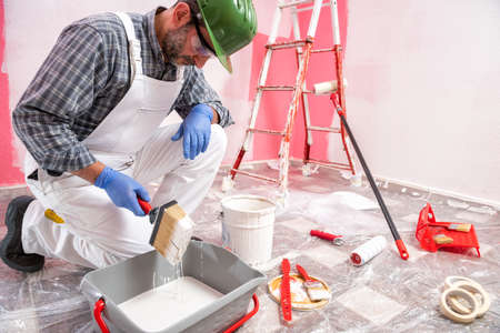 Caucasian house painter worker in white overalls, with helmet and goggles he prepares the white paint to paint the pink wall. Construction industry. Work safety.