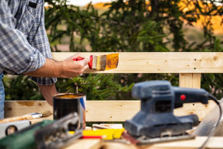 Adult craftsman carpenter with the brush painting the boards of a wooden fence. Housework do it yourself. Stock Photography.