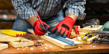 Craftsman adult carpenter with his hands protected by work gloves, tracing the cutting line on a wooden table. Housework do it yourself. Stock photography.