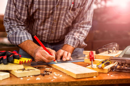 Adult craftsman carpenter with pencil and ruler tracing the cutting line on a wooden table. Housework do it yourself. Stock photography. Glow sunset. Imagens