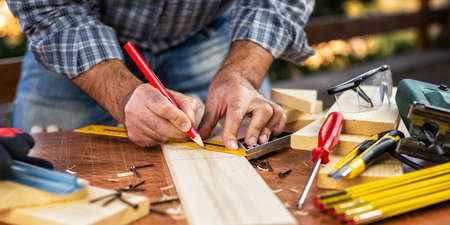 Adult carpenter with a pencil and square carpenter. Construction industry, housework do it yourself. Stock photography.